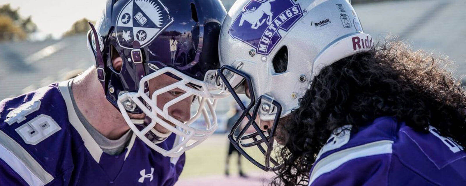 Two Football Players from Western University huddled together preparing for a game